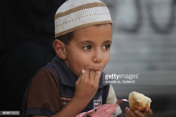 A displaced Iraqi boy who fled the town of Hawija eats food as he takes refuge with his family in the nearby town of Sharqat around 80 kilometres...