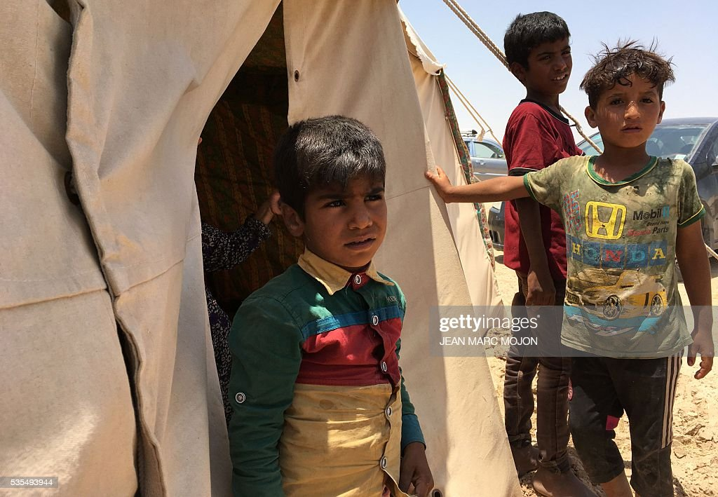 Displaced Iraqi boys stand on May 29, 2016 in front of a tent at a newly-opened camp in the government-held town of Amriyat al-Fallujah 50 kilometres (30 miles) southwest of Baghdad, which was set up to shelter people fleeing violence around the city of Fallujah. The Norwegian Refugee Council, which runs the camp in Amriyat al-Fallujah, says around 3,000 people have managed to flee the area and reach displacement camps since Iraqi forces launched an operation against the Islamic State a week ago. The biggest wave of arrivals so far was Saturday night and included mostly exhausted and hungry women and children. / AFP / Jean Marc MOJON