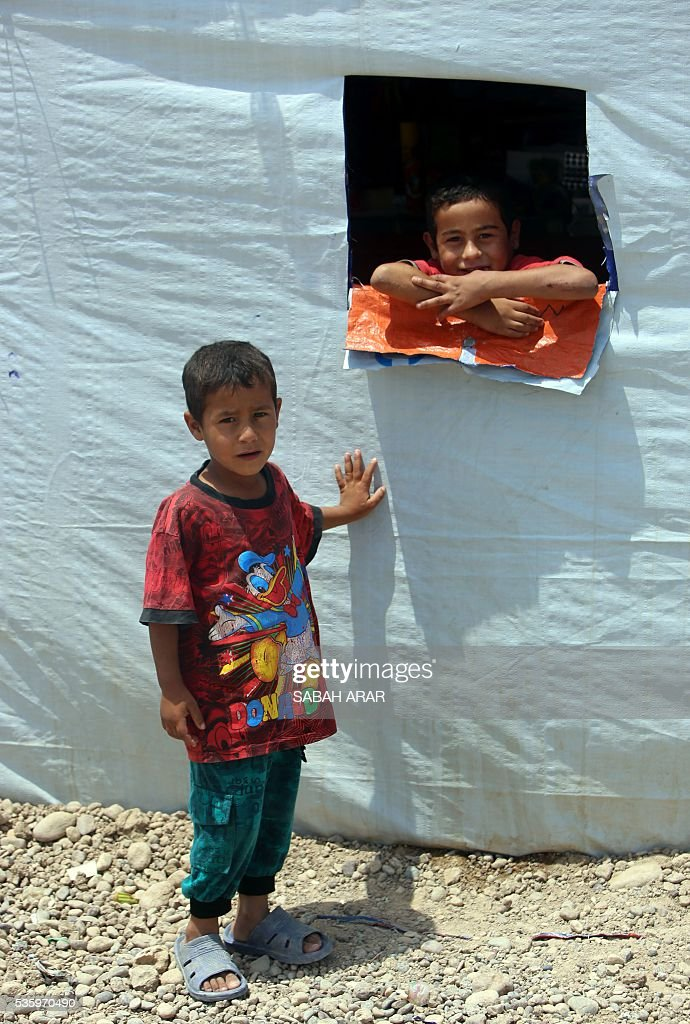 Displaced Iraqi boys stand on May 31, 2016 at the Alexanzan camp in the Dora neighbourhood on the southern outskirts of Baghdad where they are taking shelter after they were displaced from the Jbeil, a village near the embattled Iraqi city of Fallujah due to clashes between pro-government forces and the Islamic State (IS) group. Only a few hundred families have managed to slip out of the Fallujah area ahead of the assault on the city, with an estimated 50,000 civilians still trapped inside, sparking fears the jihadists could try to use them as human shields. ARAR