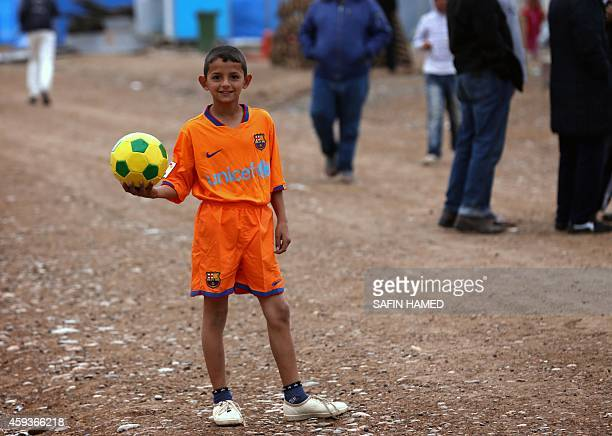 A displaced Iraqi child poses for a picture with an FC Barcelona kit he received from Isaac Tutumlu Lopez a representative of FC Barcelona and...
