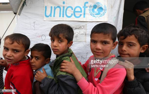 Displaced Iraqi children from the former embattled city of Mosul queue up outside a United Nations Childrens Fund school at the Hasan Sham camp some...