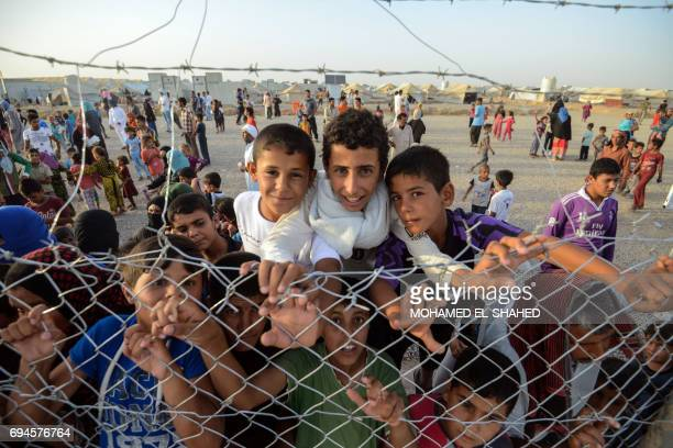 CORRECTION Displaced Iraqi children stand behind a fence at the Hasan Sham camp for internally displaced people on June 10 2017 / AFP PHOTO / MOHAMED...