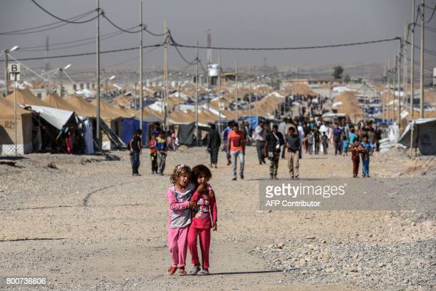 Displaced Iraqi children who fled the fighting in Mosul walk at the Salamya camp for internally displaced people south of the embattled city in the...