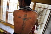 A displaced Iraqi Christian displays a tattoo of Christ on the Cross at Saint Joseph's church where he is living with hundreds of other Christians...