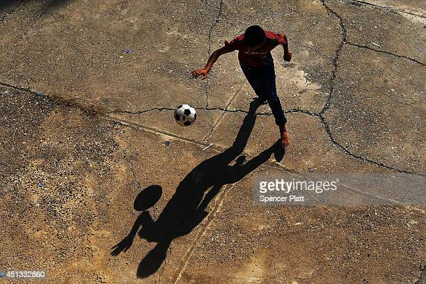 A displaced Iraqi Christian plays soccer in the courtyard of Saint Joseph's church after having to flee his district with hundreds of others on June...