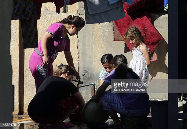 Displaced Iraqi Christian women and children cook in the Mar Yousef church in the Christian village of Ankawa north of Arbil the capital of the...