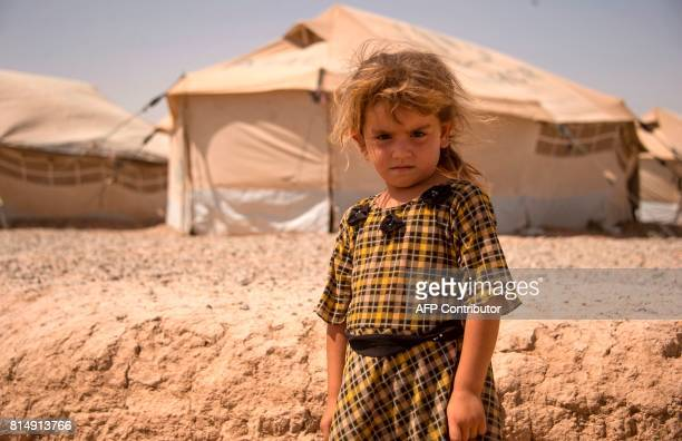 A displaced Iraqi girl looks on at a camp set up to shelter civilians fleeing violence in the northern city of Mosul on July 15 2016 in Debaga east...
