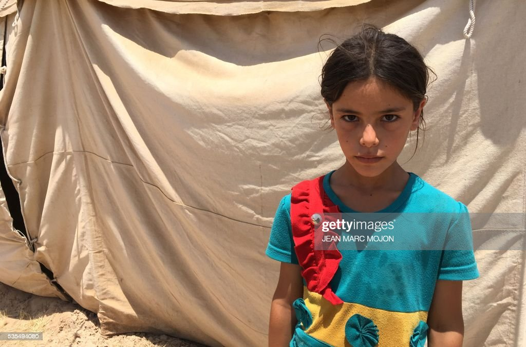 A displaced Iraqi girl poses for a picture on May 29, 2016 in front of a tent at a newly-opened camp in the government-held town of Amriyat al-Fallujah 50 kilometres (30 miles) southwest of Baghdad, which was set up to shelter people fleeing violence around the city of Fallujah. The Norwegian Refugee Council, which runs the camp in Amriyat al-Fallujah, says around 3,000 people have managed to flee the area and reach displacement camps since Iraqi forces launched an operation against the Islamic State a week ago. The biggest wave of arrivals so far was Saturday night and included mostly exhausted and hungry women and children. / AFP / Jean Marc MOJON