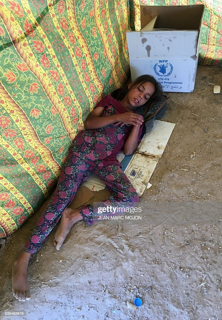 A displaced Iraqi girl sleeps on May 29, 2016 inside a tent at a newly-opened camp in the government-held town of Amriyat al-Fallujah 50 kilometres (30 miles) southwest of Baghdad, which was set up to shelter people fleeing violence around the city of Fallujah. The Norwegian Refugee Council, which runs the camp in Amriyat al-Fallujah, says around 3,000 people have managed to flee the area and reach displacement camps since Iraqi forces launched an operation against the Islamic State a week ago. The biggest wave of arrivals so far was Saturday night and included mostly exhausted and hungry women and children. / AFP / Jean Marc MOJON