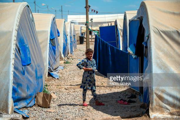 A displaced Iraqi girl smiles as she stands outside her family's tent at a camp for Internally Displaced People in Hammam alAlil south of Mosul on...