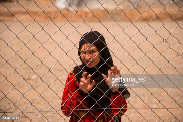 A displaced Iraqi girl stands behind a fence at a camp set up to shelter civilians fleeing violence in the northern city of Mosul on July 15 2016 in...