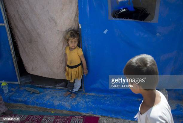 TOPSHOT A displaced Iraqi girl stands outside her family's tent at a camp for Internally Displaced People in Hammam alAlil south of Mosul on May 22...