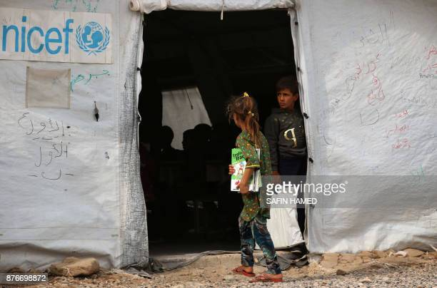 A displaced Iraqi girl walks into a United Nations Childrens Fund school at the Hasan Sham camp some 40 kilometres east of Arbil in northern Iraq on...