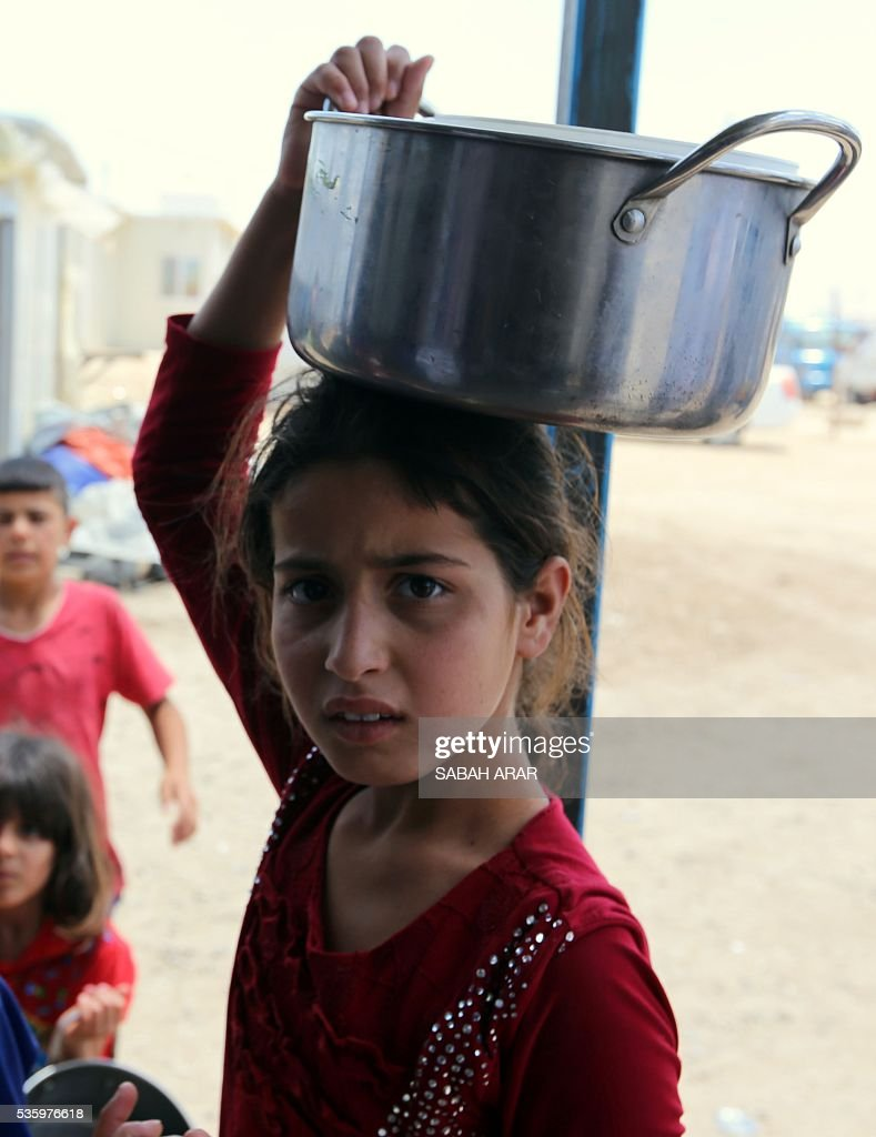 A displaced Iraqi girl who fled fighting between government forces and the Islamic State (IS) group in Anbar province lines up to collect donated food at the Alexanzan camp in the Dora neighbourhood on the southern outskirts of Baghdad on May 31, 2106. Only a few hundred families have managed to slip out of Anbar's Fallujah area ahead of the assault on the city, with an estimated 50,000 civilians still trapped inside, sparking fears the jihadists could try to use them as human shields ARAR
