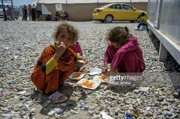 Displaced Iraqi girls eat outside their tent at a camp for Internally Displaced People in Hammam alAlil south of Mosul on May 22 2017 The exodus of...