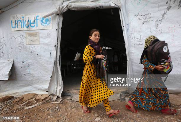 Displaced Iraqi girls hold their schoolbags at a United Nations Childrens Fund school at the Hasan Sham camp some 40 kilometres east of Arbil in...