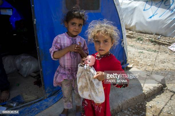 Displaced Iraqi girls stand outside their family's tent at a camp for Internally Displaced People in Hammam alAlil south of Mosul on May 22 2017 The...