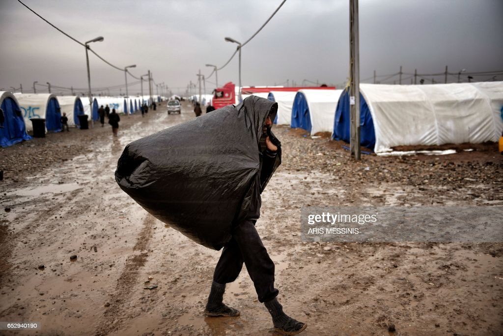 A displaced Iraqi man from Mosul walks under the rain at the Hamam al-Alil camp on March 13, 2017, during the government forces ongoing offensive to retake the western parts of the city from Islamic State (IS) group fighters. /