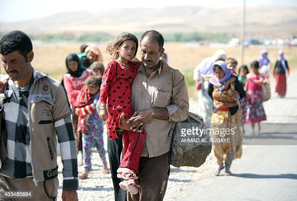 A displaced Iraqi man from the Yazidi community carries his daughter as they cross the IraqiSyrian border at the Fishkhabur crossing in northern Iraq...