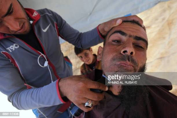 TOPSHOT A displaced Iraqi man has his beard shaved at the Hammam alAlil camp for internally displaced people south of Mosul on May 25 as government...