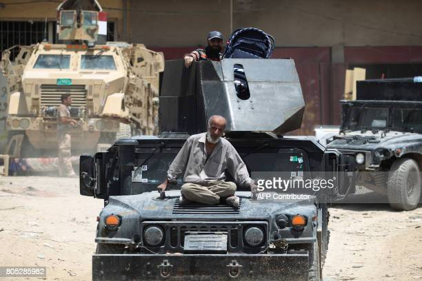 A displaced Iraqi man sits on an Iraqi forces tank as he's being evacuated from the Old City of Mosul on July 1 2017 where Iraqi forces are battling...