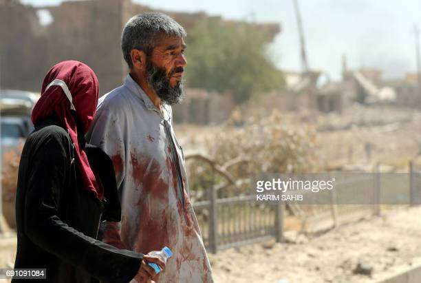 A displaced Iraqi man walks with his daughter as they evacuate their home in western Mosul's Zanjili neighbourhood on June 1 2017 during ongoing...