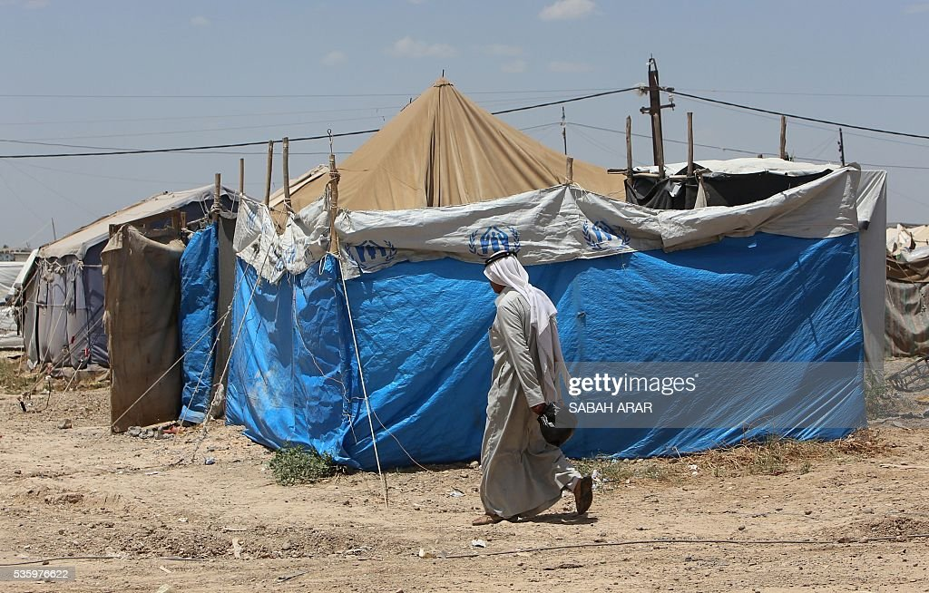 A displaced Iraqi man who fled fighting between government forces and the Islamic State (IS) group in Anbar province walks on May 31, 2015 at the Alexanzan camp in the Dora neighbourhood on the southern outskirts of Baghdad on May 31, 2106. Only a few hundred families have managed to slip out of Anbar's Fallujah area ahead of the assault on the city, with an estimated 50,000 civilians still trapped inside, sparking fears the jihadists could try to use them as human shields ARAR