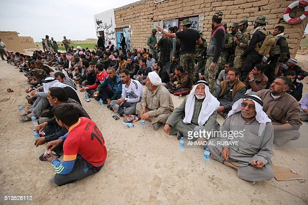Displaced Iraqi men sit on the ground as progovernment forces sort them out during an operation in the desert West of the Iraqi city of Samarra aimed...