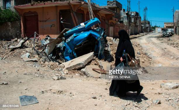 TOPSHOT A displaced Iraqi walks past a destroyed vehicle after residents were evacuated from their homes in a neighbourhood of west Mosul on May 17...