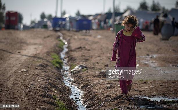 A displaced Iraqi who was forced to flee her home because of Islamic State's advance earlier this year walks past tents that have been erected at the...