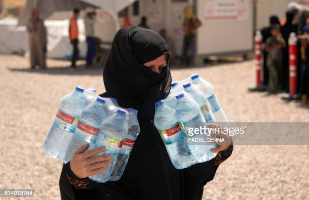 A displaced Iraqi woman carries water bottles at a camp set up to shelter civilians fleeing violence in the northern city of Mosul on July 15 2016 in...