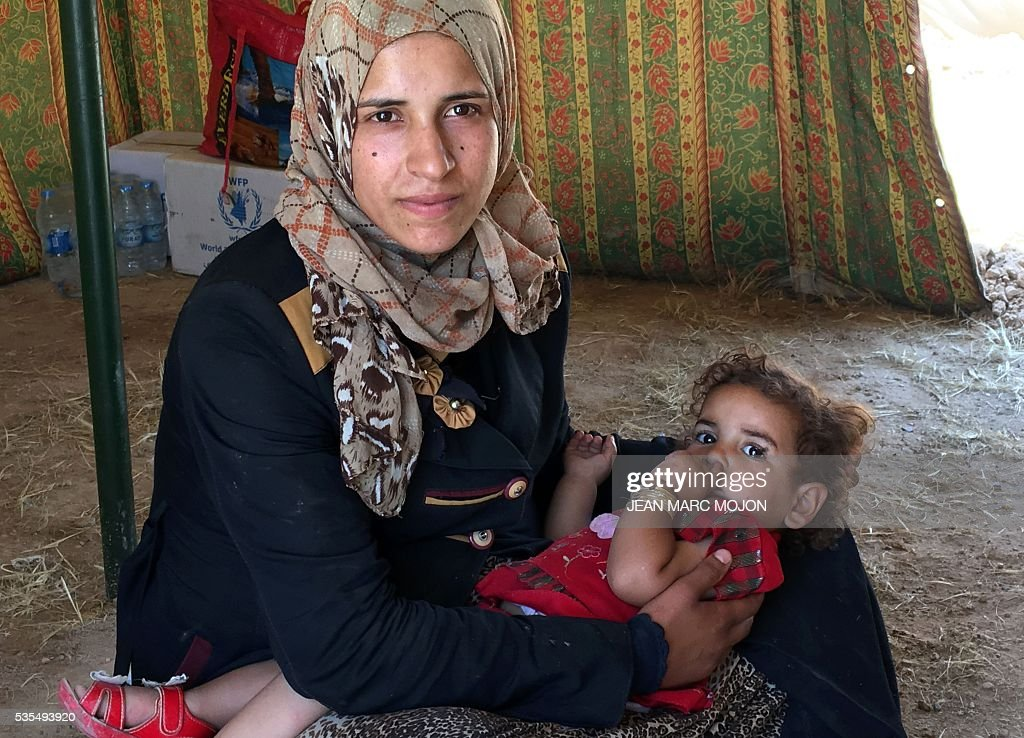 A displaced Iraqi woman cradles her sleeping child inside a tent at a newly-opened camp in the government-held town of Amriyat al-Fallujah 50 kilometres (30 miles) southwest of Baghdad, on May 29, 2016, which was set up to shelter people fleeing violence around the city of Fallujah. The Norwegian Refugee Council, which runs the camp in Amriyat al-Fallujah, says around 3,000 people have managed to flee the area and reach displacement camps since Iraqi forces launched an operation against the Islamic State a week ago. The biggest wave of arrivals so far was Saturday night and included mostly exhausted and hungry women and children. / AFP / Jean Marc MOJON