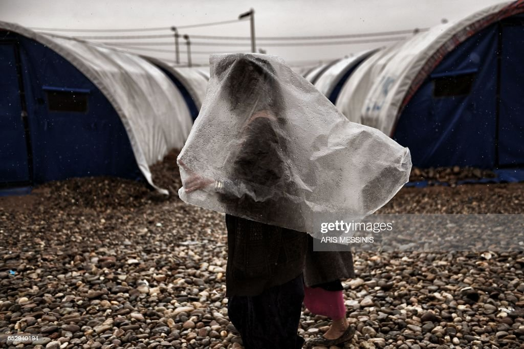 TOPSHOT - A displaced Iraqi woman from Mosul walks under the rain at the Hamam al-Alil camp on March 13, 2017, during the government forces ongoing offensive to retake the western parts of the city from Islamic State (IS) group fighters. /