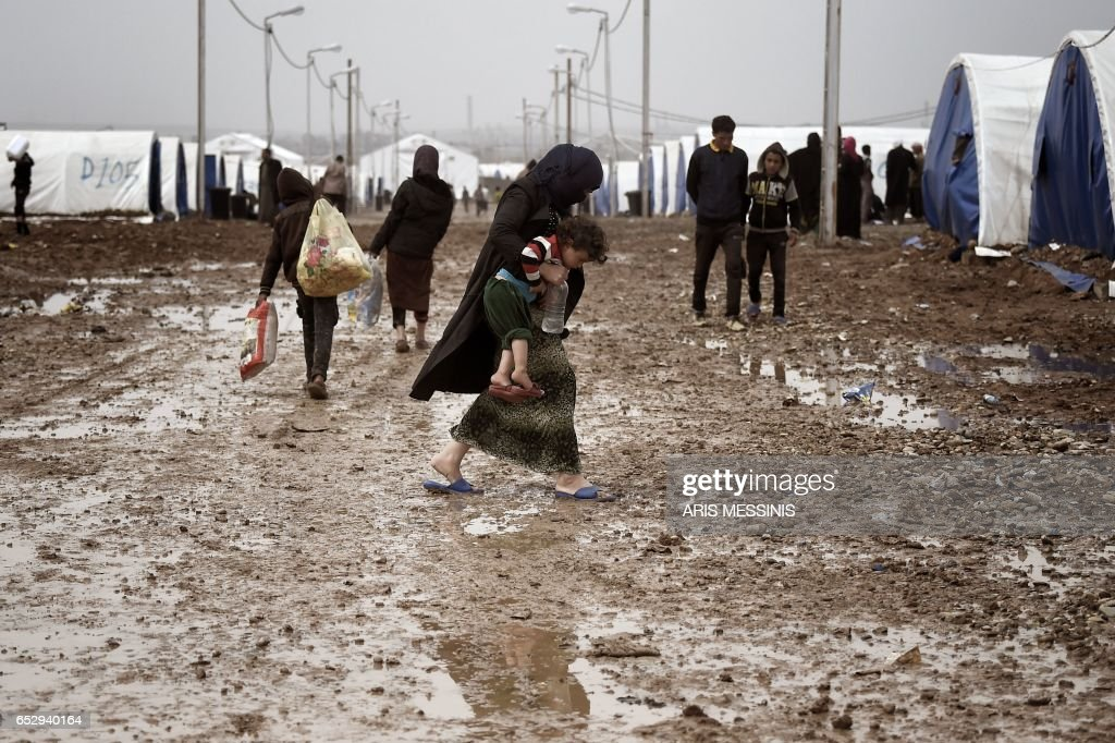 A displaced Iraqi woman from Mosul walks under the rain with her child at the Hamam al-Alil camp on March 13, 2017, during the government forces ongoing offensive to retake the western parts of the city from Islamic State (IS) group fighters. /
