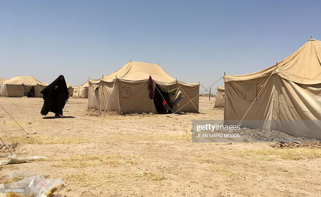 A displaced Iraqi woman walks between tents at a newly-opened camp in the government-held town of Amriyat al-Fallujah 50 kilometres (30 miles) southwest of Baghdad, on May 29, 2016, which was set up to shelter people fleeing violence around the city of Fallujah. The Norwegian Refugee Council, which runs the camp in Amriyat al-Fallujah, says around 3,000 people have managed to flee the area and reach displacement camps since Iraqi forces launched an operation against the Islamic State a week ago. The biggest wave of arrivals so far was Saturday night and included mostly exhausted and hungry women and children. / AFP / Jean Marc MOJON