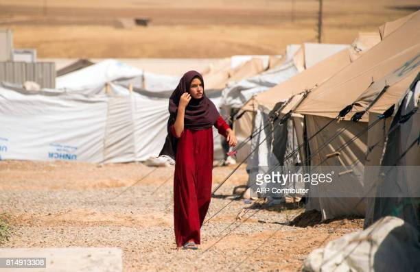 A displaced Iraqi woman walks past tents at the Hasan Sham camp some 30 kilometres east of Mosul on July 15 2017 / AFP PHOTO / FADEL SENNA