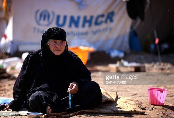 A displaced Iraqi woman who fled her home due to attacks by jihadists from the Islamic State group sits holding prayer beads at the Harsham refugee...