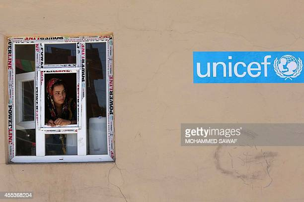 A displaced Iraqi woman who has fled the offensive led by the Islamic State jihadist group stands behind a window on September 13 2014 at a camp for...