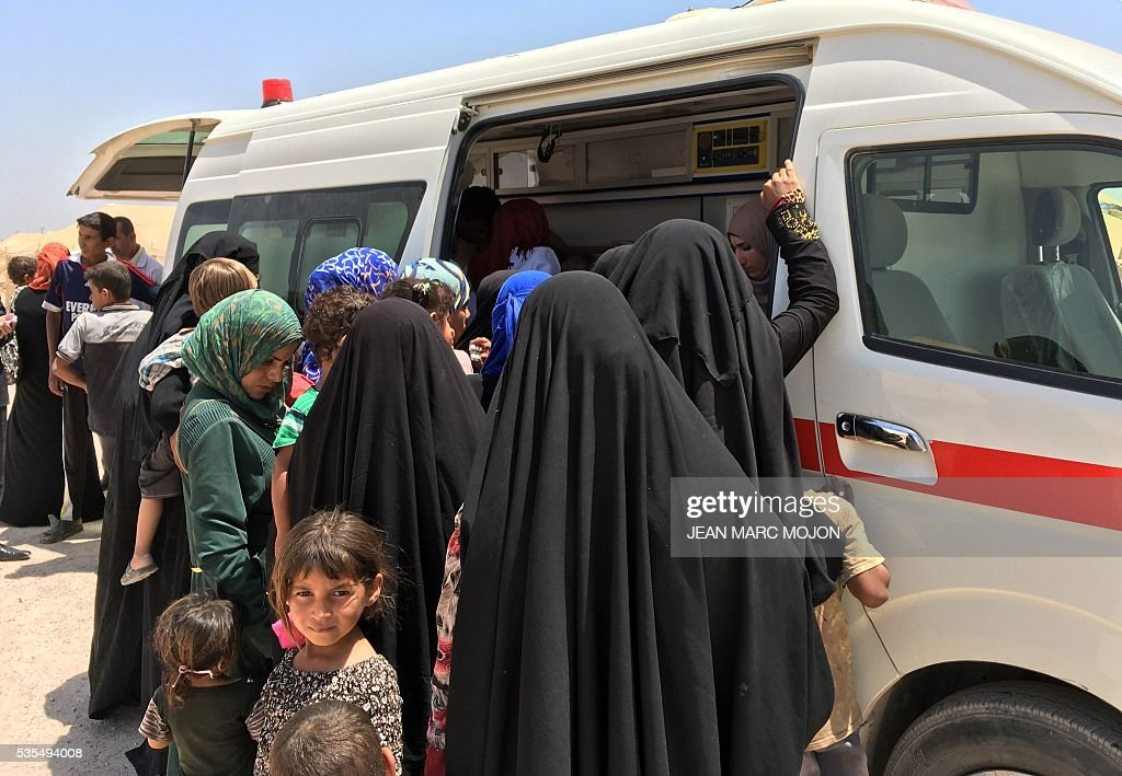 Displaced Iraqi women and children swarm a Red Crescent ambulance handing out medicine at a newly-opened camp in the government-held town of Amriyat al-Fallujah 50 kilometres (30 miles) southwest of Baghdad, on May 29, 2016, which was set up to shelter people fleeing violence around the city of Fallujah. The Norwegian Refugee Council, which runs the camp in Amriyat al-Fallujah, says around 3,000 people have managed to flee the area and reach displacement camps since Iraqi forces launched an operation against the Islamic State a week ago. The biggest wave of arrivals so far was Saturday night and included mostly exhausted and hungry women and children. / AFP / Jean Marc MOJON