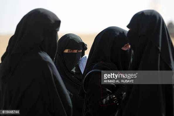 Displaced Iraqi women from the Bajwaniyah village about 30 kms south of Mosul who fled fighting in the Mosul area look on as they approach security...