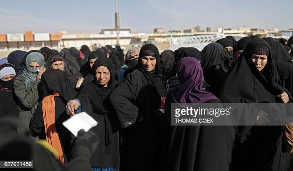 Displaced Iraqi women queue to receive food distribution from a British charity on December 4 2016 in the village of Gogjali on the eastern edge of...