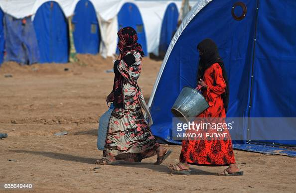Displaced Iraqi women walk carrying buckets at the AlAgha camp where Iraqi families from the nearby villages of Tal Afar southwest of Mosul are...