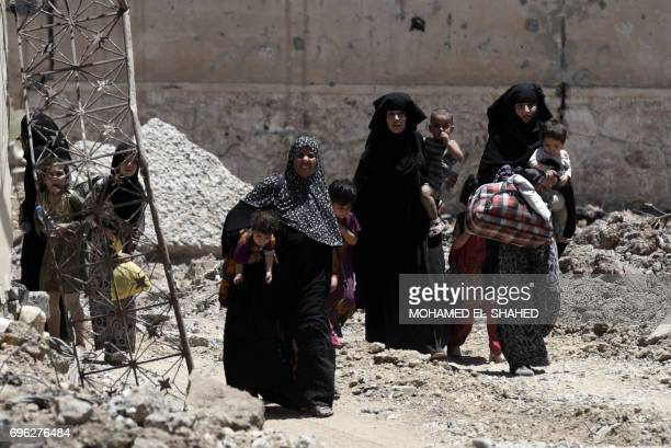 TOPSHOT Displaced Iraqi women walk towards Iraq forces as they flee their homes in Mosul's western AlShifa district on June 15 during the ongoing...