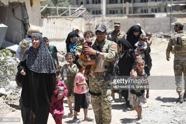 Displaced Iraqi women walk towards Iraq forces as they flee their homes in Mosul's western AlShifa district on June 15 during the ongoing offensive...