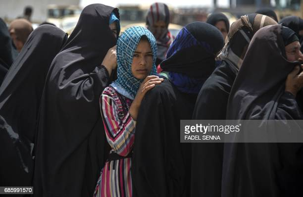 TOPSHOT Displaced Iraqi women who fled their homes due to the ongoing fighting against Islamic State group jihadists queue to receive water and food...