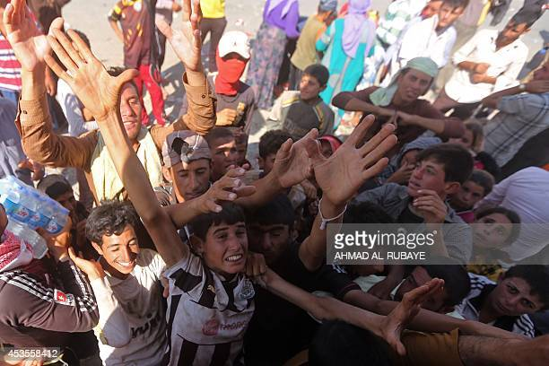 Displaced Iraqi Yazidis who fled a jihadist onslaught on Sinjar gather to collect bottles of water at the Bajid Kandala camp in Kurdistan's western...