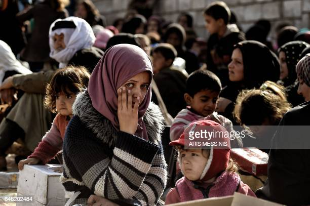TOPSHOT Displaced Iraqi young woman looks towards the camera as she gathers with others to flee the city of Mosul while Iraqi forces battle against...