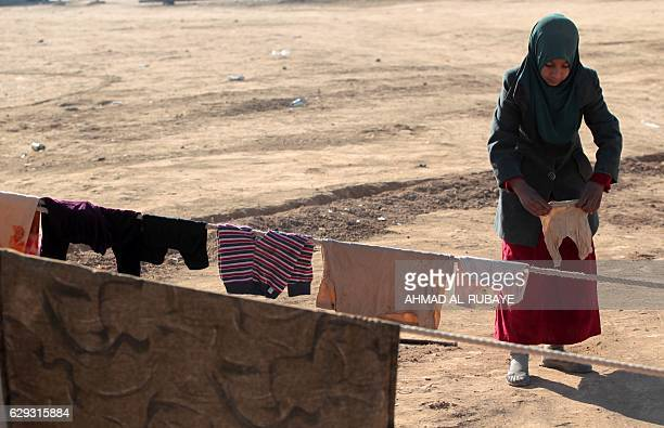 A displaced Iraqi youth from the outskirts of the city of Tal Afar hangs clothes at a makeshift camp on December 12 2016 in the village of Khalif...
