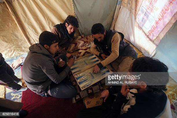 Displaced Iraqi youth from the outskirts of the city of Tal Afar play at a makeshift camp on December 12 2016 in the village of Khalif Saleh south of...