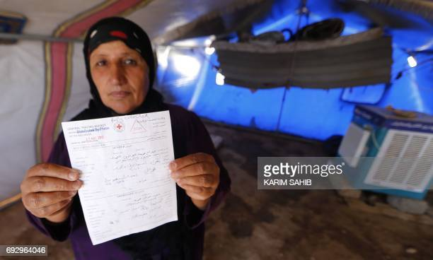 Displaced Iraqi Yusra Mohammed holds a letter from the Central Tracing Agency of the Red Cross stating the whereabouts of her two teenage sons as she...